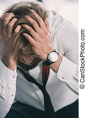 front view of stressed business man holding his head with hands