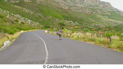 Front view of stylish young woman doing skateboard trick on downhill at countryside road 4k