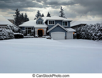 Front view of suburban home with snow storm ending in early morning light