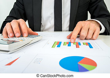 Front view of the hands of a accountant analysing a bar graph