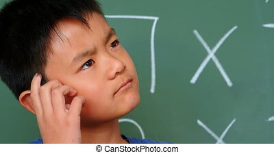 Front view of thoughtful Asian schoolboy scratching his head...