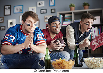 Front view of three men watching American football