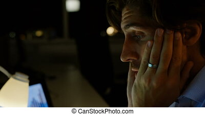 Front view of tired young Caucasian male executive working on computer at desk in modern office 4k