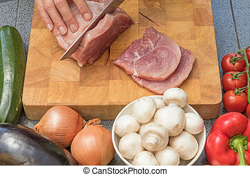 Front view of woman slicing meat on a wooden board closeup