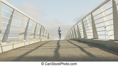 Front view of woman wearing hijab running - Low angle front ...