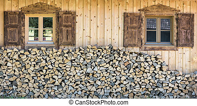 front view of wooden chalet house with wood stack and window shutter