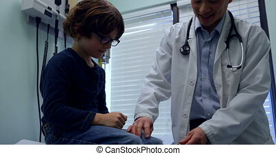 Front view of young asian male doctor examining caucasian boy patient knee in a clinic 4k