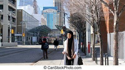 Front view of young Asian woman in hijab using mobile phone in the city 4k