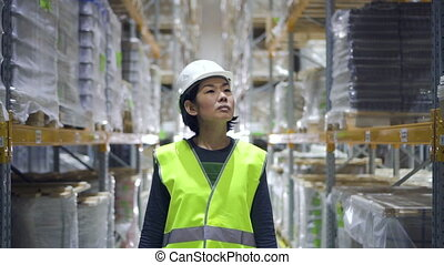 Front view of young asian woman walking on warehouse interior during working day.