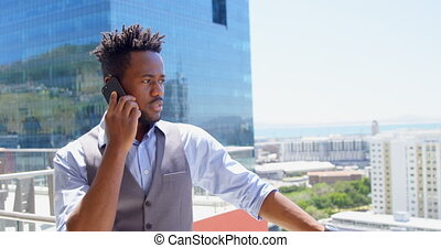 Front view of young black businessman talking on mobile phone in balcony of modern office 4k