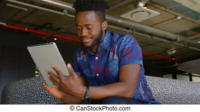 Front view of young black businessman working on digital tablet in a modern office 4k