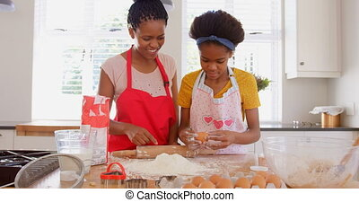 Front view of young black daughter cracking egg on flour in kitchen of comfortable home 4k
