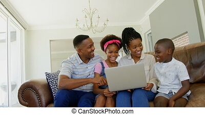 Front view of young black family sitting on the couch and using laptop in a comfortable home 4k