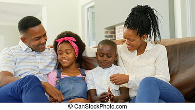 Front view of young black family sitting on the couch in a comfortable home 4k