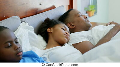 Front view of young black family sleeping together on bed in bedroom of comfortable home 4k
