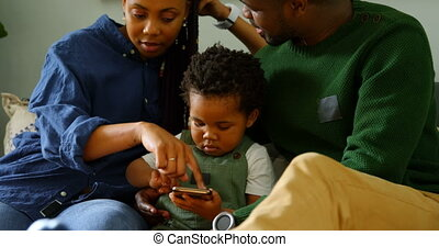 Front view of young black family using mobile phone and sitting on the couch in comfortable home 4k