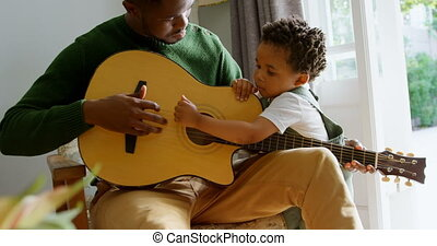 Front view of young black father and little son playing guitar in living room of comfortable home 4