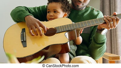 Front view of young black father and little son playing guitar in living room of comfortable home 4k