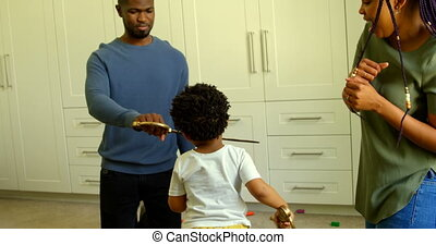 Front view of young black father and son playing with toy sword in a comfortable home 4k