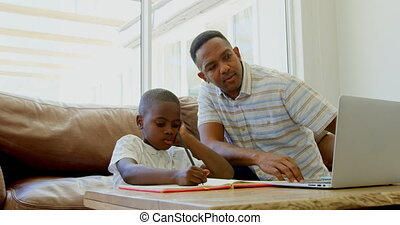 Front view of young black father helping his son with homework in a comfortable home 4k