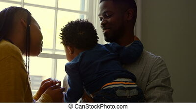 Front view of young black father holding his baby in a comfortable home 4k