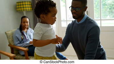 Front view of young black father playing with his son in living of comfortable home 4k