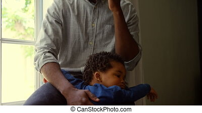 Front view of young black father talking on mobile phone with baby in a comfortable home 4k