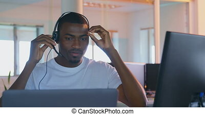 Front view of young black male executive working on computer at desk in modern office 4k