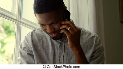 Front view of young black man talking on mobile phone in a comfortable home 4k