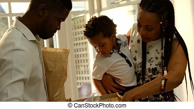 Front view of young black mother and son looking in grocery bag in kitchen of comfortable home 4k