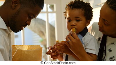 Front view of young black mother feeding cupcake to her son in kitchen of comfortable home 4k