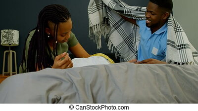 Front view of young black parents playing with their son on bed in a comfortable home 4k