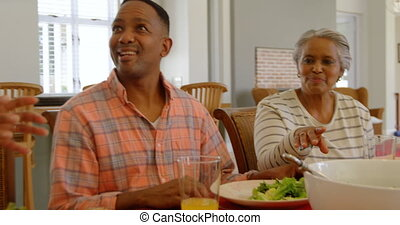 Front view of young black woman serving food to her family at dining table in a comfortable home 4k