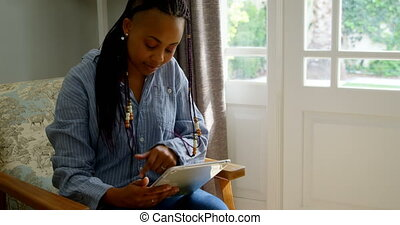 Front view of young black woman using digital tablet in living room of comfortable home 4k