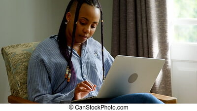 Front view of young black woman working on laptop in a comfortable home. She is sitting on the couch 4k