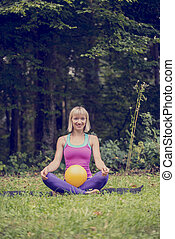 Front view of young blonde woman making a Lotus position in cross-legged