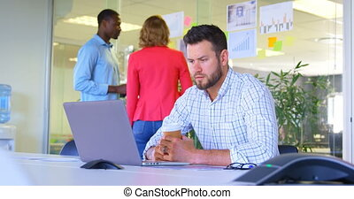 Front view of young caucasian businessman working on laptop in modern office 4k