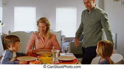 Front view of young Caucasian family having food at dining table in a comfortable home 4k
