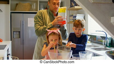 Front view of young Caucasian father and children preparing food in kitchen of comfortable home 4k