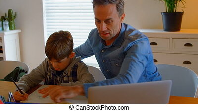 Front view of young Caucasian father helping son with homework at table in a comfortable home 4k