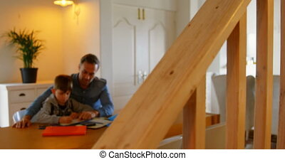 Front view of young Caucasian father helping son with homework in a comfortable home 4k