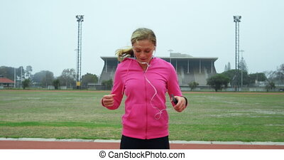 Front view of young Caucasian female athlete dancing at sports venue. She is listening music 4k