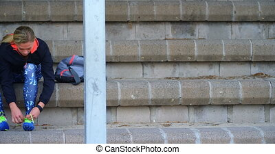 Front view of young Caucasian female athlete tying shoes at sport venue. She is getting ready 4k