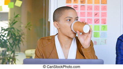 Front view of young caucasian female executive having coffee at desk in modern office 4k