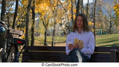 Front view of young Caucasian man having coffee in the park 4k