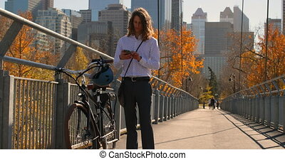 Front view of young Caucasian man using mobile phone on the bridge 4k
