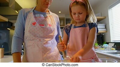Front view of young Caucasian mother and daughter preparing dough in a bowl 4k
