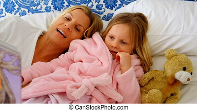 Front view of young Caucasian mother and daughter reading story book on bed in a comfortable home 4k
