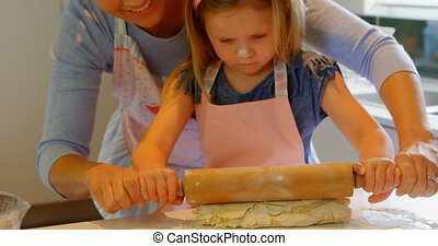 Front view of young Caucasian mother and daughter rolling dough in kitchen of comfortable home 4k