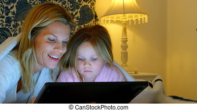 Front view of young Caucasian mother and daughter using digital tablet in bedroom at home 4k